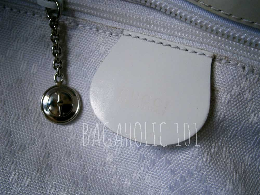 38cd4e04023 A GG medallion zipper pull on a white Gucci nylon canvas tote bag - Tips on
