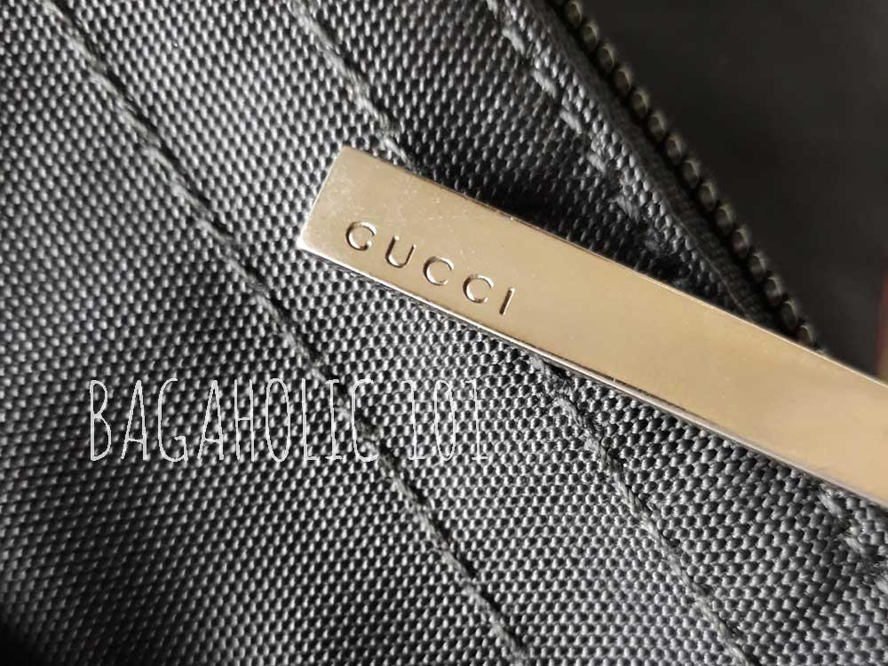 a5ae4398a00 A black nylon canvas Gucci tote bag with a metal zipper pull marked with  GUCCI -