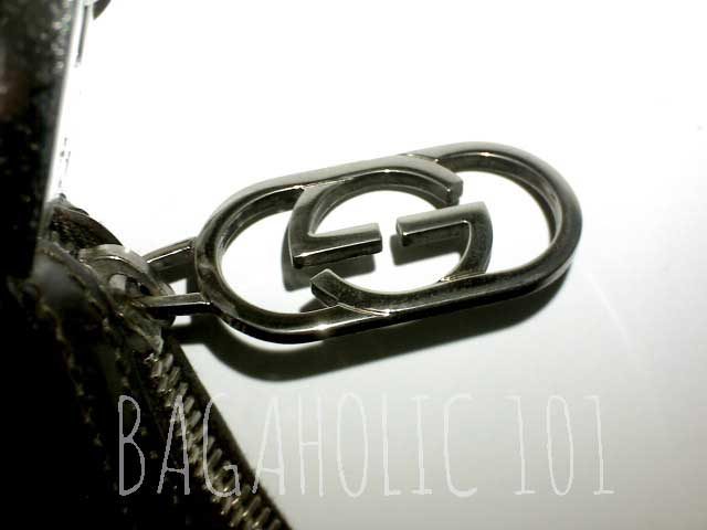 A black patent leather bag with a GG metal zipper pull - Tips on Original Gucci Bags on Sale - How to Tell if a Gucci Bag is Real