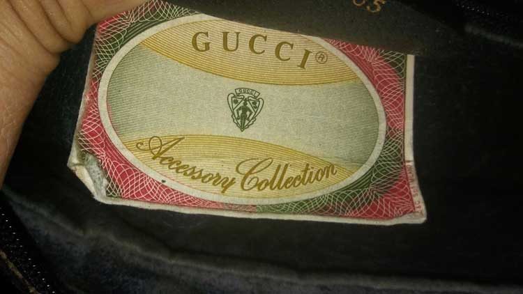 A vintage Gucci bag with a paper tag with GUCCI Accessory Collection written on it - Vintage Gucci Bag Authentication - Gucci Serial Number Check - How to Tell if a Gucci Bag is Real