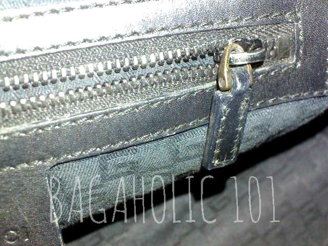A wooden handle tote with a standard plain side leather zipper pull