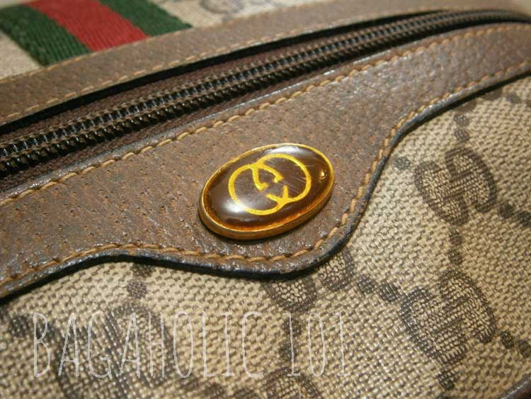 GG logo in an enamel in front of a vintage Gucci accessory collection bag - Vintage Gucci Bag Authentication - Gucci Serial Number Check - How to Tell if a Gucci Bag is Real
