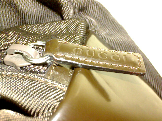 Gucci marked leather zipper pull from a nylon canvas and patent leather Gucci bag