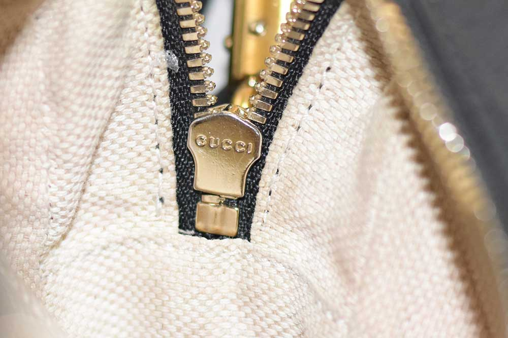 Underneath of a zipper marked with GUCCI A YKK marked Gucci zipper pull in contemporary bags - Tips on Original Gucci Bags on Sale - How to Tell if a Gucci Bag is Real