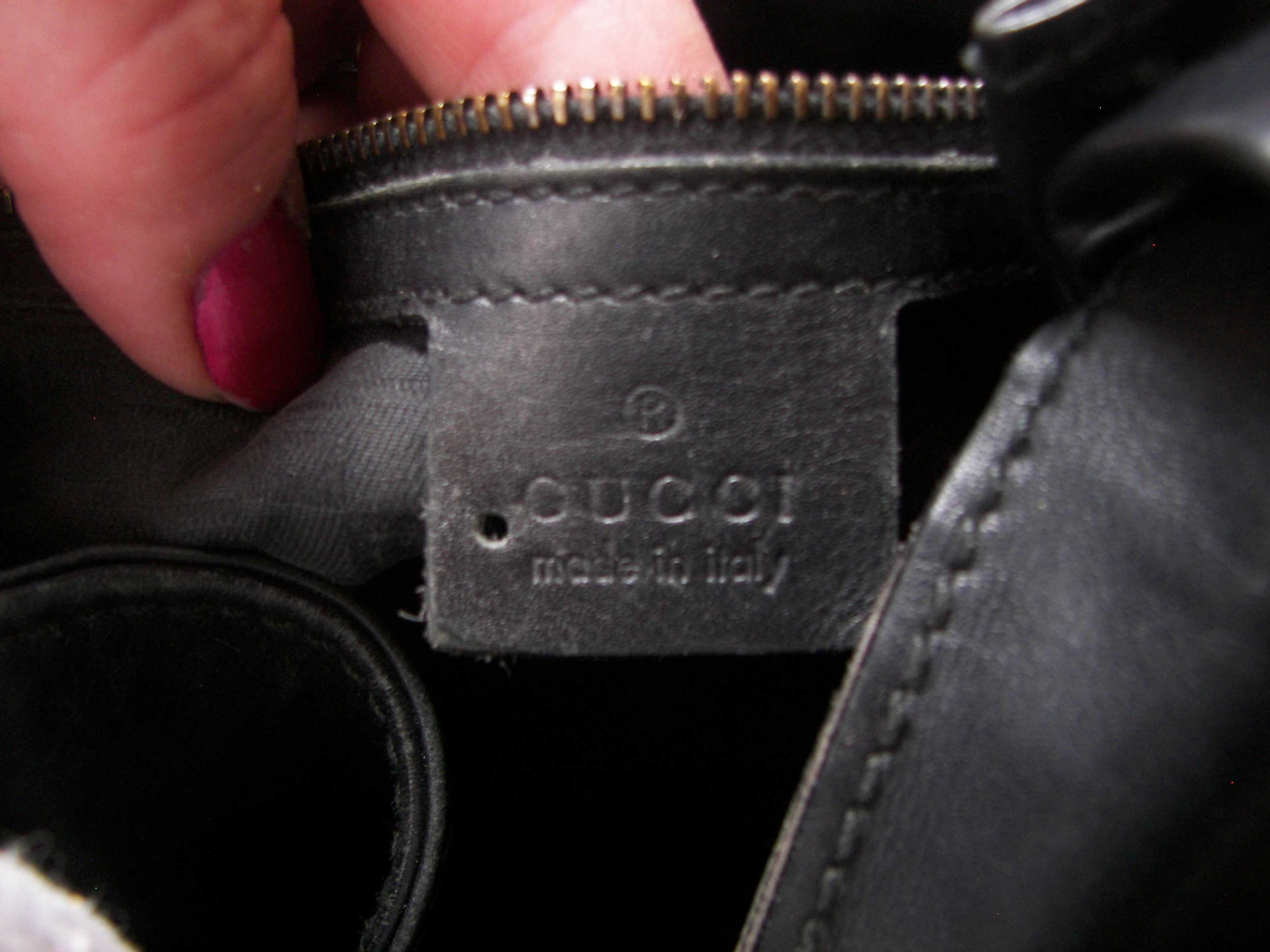 Gucci outlet bag with a hole punched through the leather tag