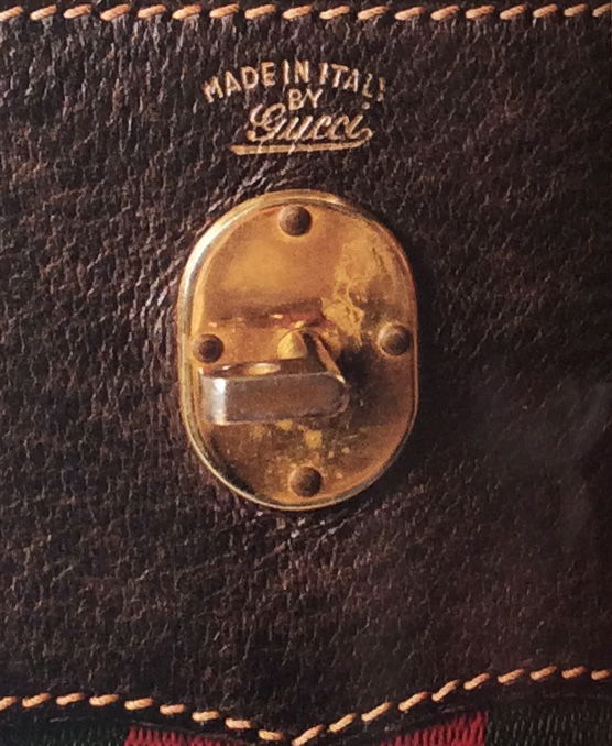 Bagaholic 101 - Gucci Heritage, Icons, and Beyond - 1960's luggage interior in all caps letters and Gucci cursive in Gold, showing 'MADE IN ITALY BY Gucci'