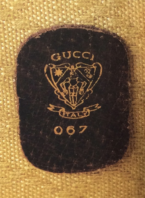 Bagaholic 101 - Gucci Heritage, Icons, and Beyond - Letters, Gucci crest, and numbers hotstamp in gold in luggage interior showing 'Gucci Italy 067'