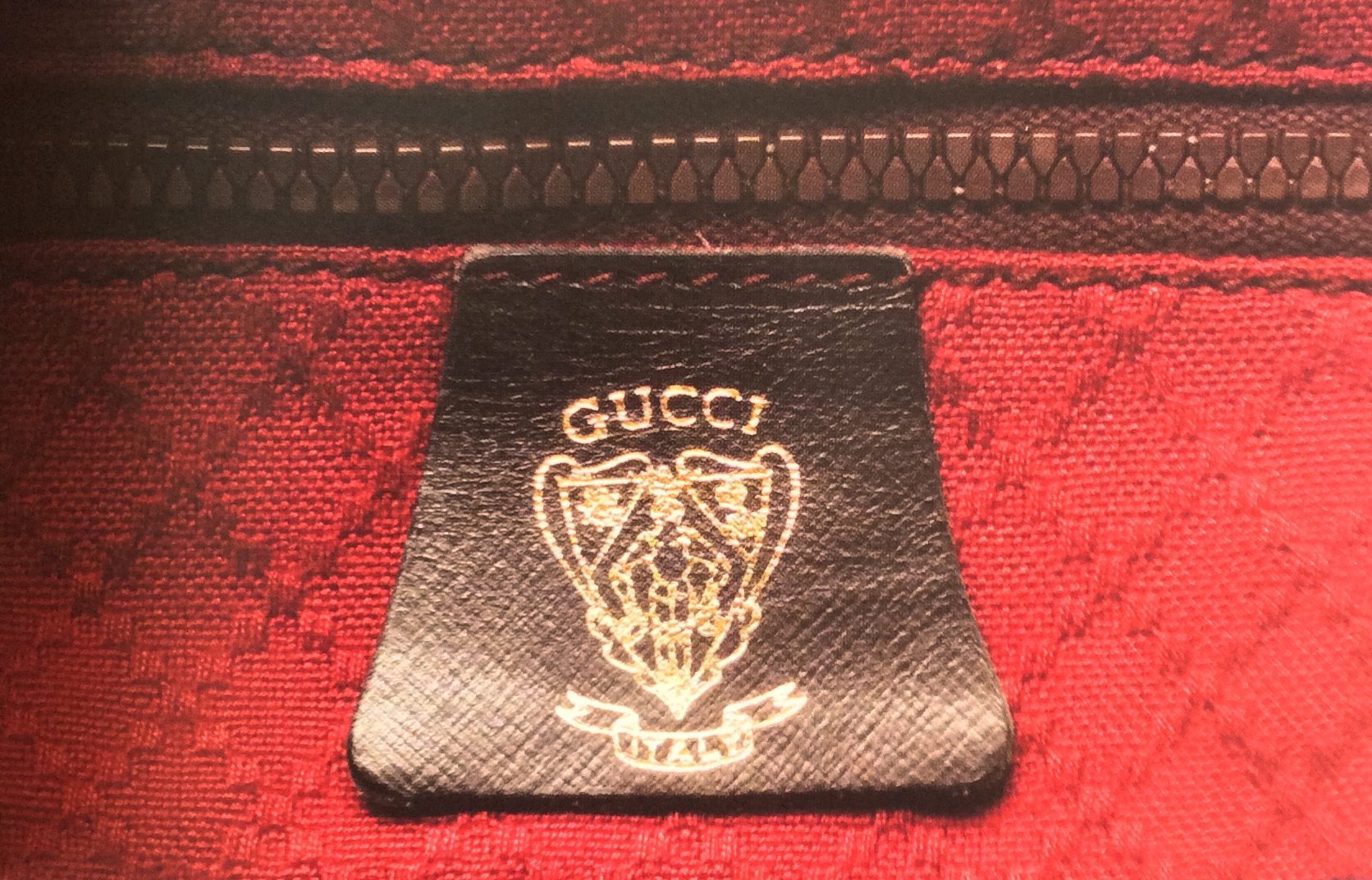 Bagaholic 101 - Gucci Heritage, Icons, and Beyond - Luggage interior with leather tag showing 'GUCCI ITALY. and the Gucci crest hotstamped in gold